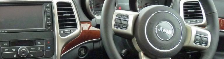 Einen Bild von ein Armaturenbrett eines Fahrzeugs der einen Fahrers Lenkrad zeigt